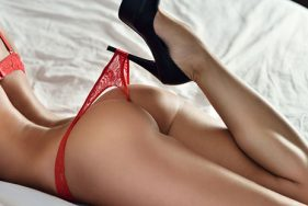 Escort girl on a bed in red lingerie