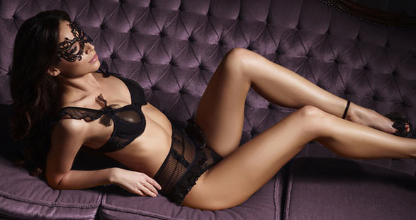 Part-time escort in sexy lingerie on a sofa